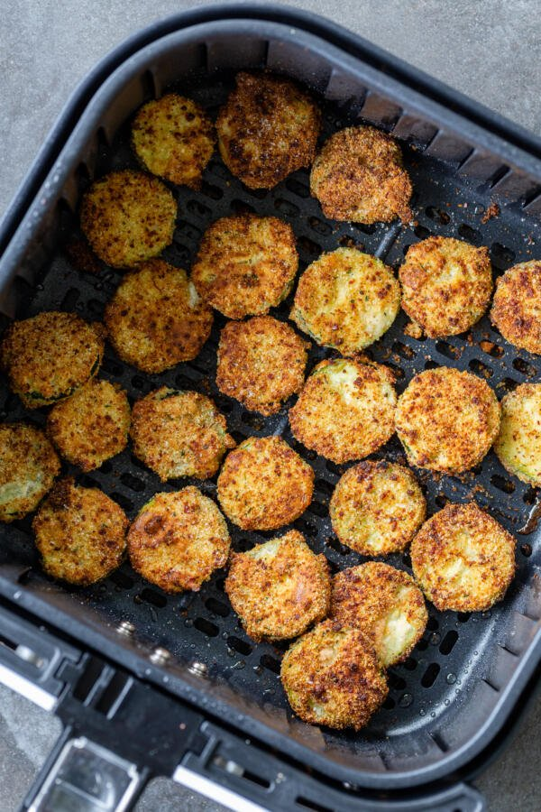 parmesan zucchini chips in air fryer basket cooked