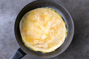 Tortilla on top of eggs in a pan