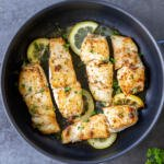 fried halibut in a pan with herbs and lemon