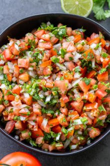 The Classic Pico de Gallo in a bowl with vegetables next to it