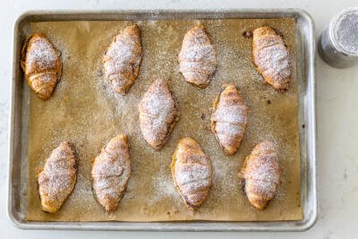 croissants with powdered sugar on a baking sheet