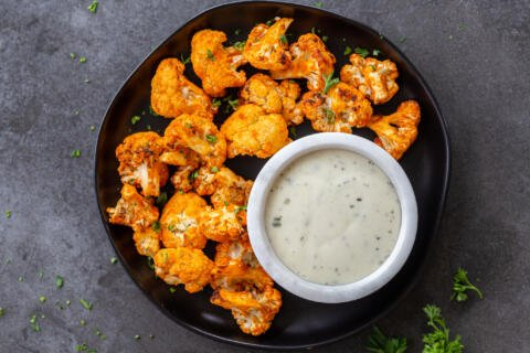 cooked cauliflower with buffalo sauce on a plate