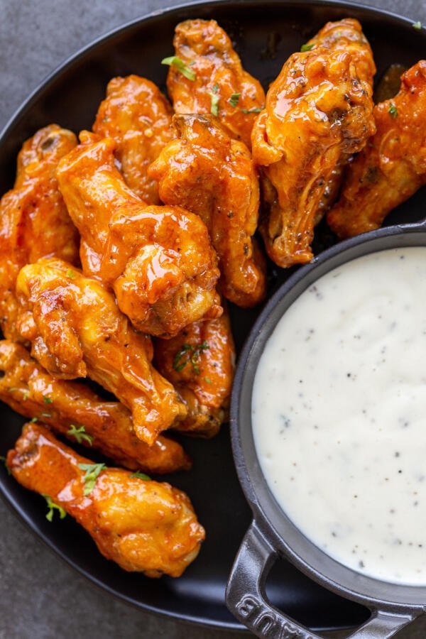 air fryer wing with buffalo sauce on a plate with ranch for dipping