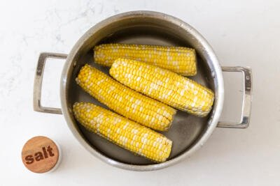 corn on a cob in a pot with salt and water