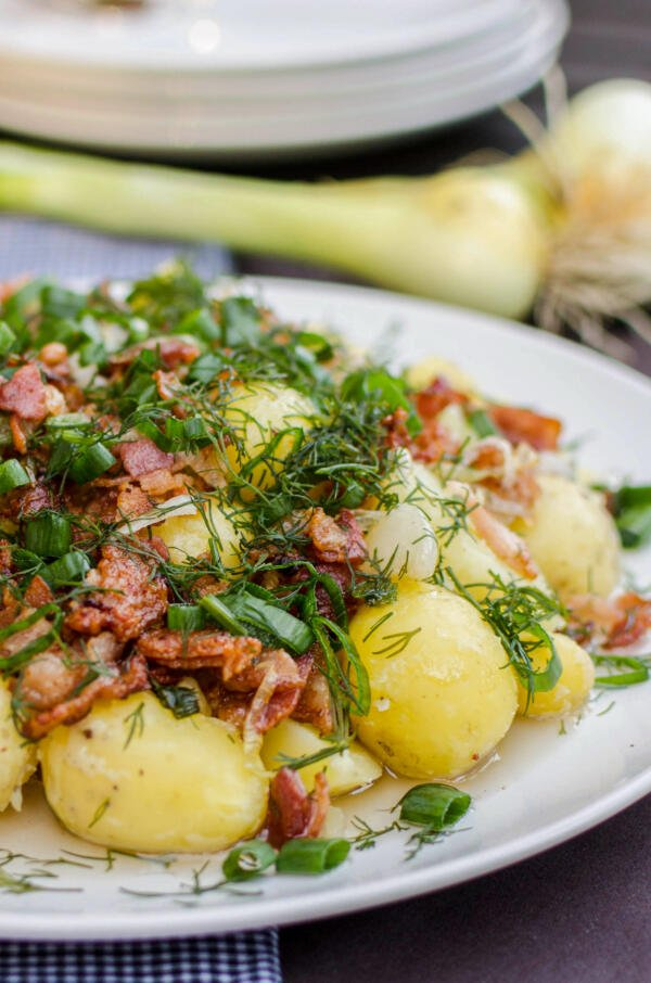 New potatoes on a plate with herbs and bacon