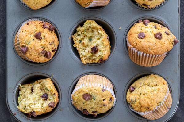 baked muffins in a muffin pan witht wo brokena part