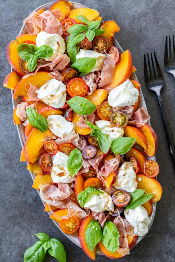 Tomato peach burrata salad on a plate